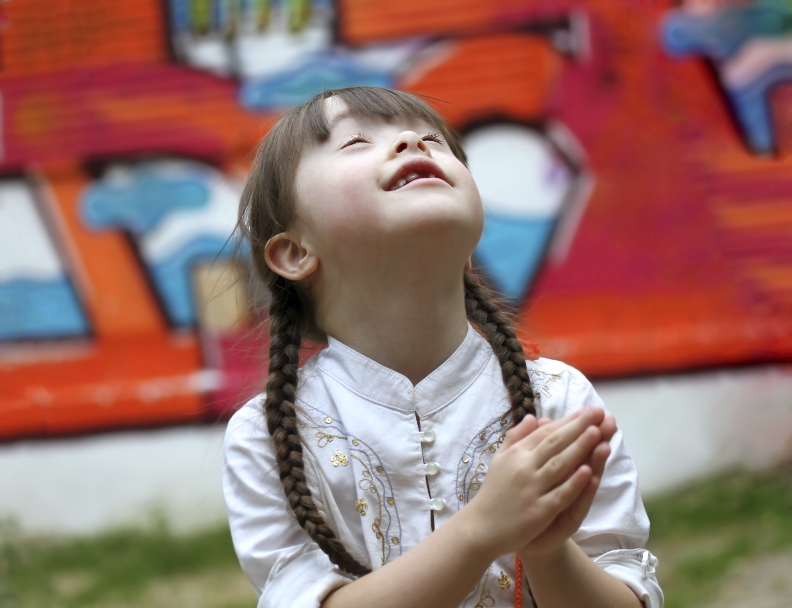 Portrait of beautiful young girl praying on the playground